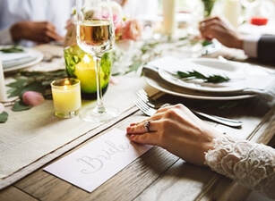 Picture of a a bride seating on her table at her wedding day. Enjoying a glass of champagne