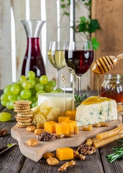 Picture of mix different cheese plate serve with green grapes.  Wine glasses with white and red wine